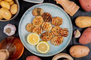 Draufsicht auf gebratene gekräuselte Kartoffelscheiben und Zitronenscheiben in Platte mit ganzem Butterknoblauch auf hölzernem Hintergrund foto