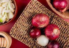 Draufsicht von roten und weißen Zwiebeln in Korbteller mit geschnittenem weißem in Schüssel und schwarzen Pfeffersamen auf rotem Hintergrund