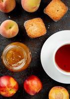 Draufsicht des Glasgefäßes der Pfirsichmarmelade mit Pfirsich-Cupcakes und einer Tasse Tee auf schwarzem und braunem Hintergrund