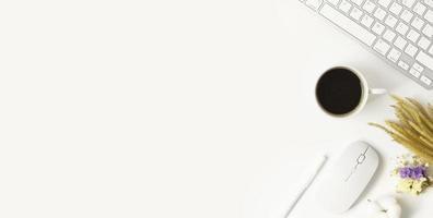 Minimaler Schreibtisch-Tisch mit Tastaturcomputer, Kaffeetasse, Maus, weißem Stift, Baumwollblumen auf einem weißen Tisch mit Kopierraum für die Eingabe Ihres Textes, weiße Arbeitsplatzzusammensetzung, flache Lage, Draufsicht foto