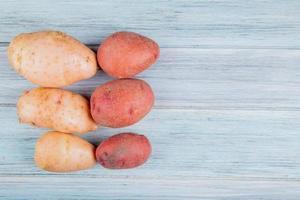 Draufsicht von rostroten und roten Kartoffeln auf der linken Seite und hölzernem Hintergrund mit Kopienraum