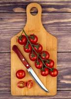 Tomaten mit Messer auf Schneidebrett auf hölzernem Hintergrund