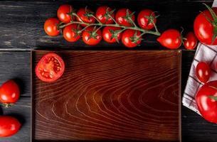 Draufsicht der halb geschnittenen Tomate im Tablett und der ganzen auf hölzernem Hintergrund foto