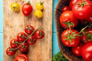 Draufsicht von geschnittenen und ganzen Tomaten auf Schneidebrett mit anderen in Korb und Koriander auf blauem Hintergrund foto