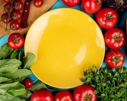 Draufsicht des Gemüses als Spinat-Basilikum-Tomatenkoriander mit Messer auf Schneidebrett und leerem Teller auf blauem Hintergrund