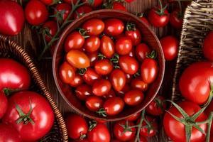 Draufsicht der Tomaten im Schüsselkorb und im Teller auf hölzernem Hintergrund