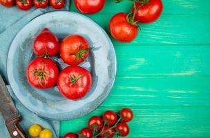 Draufsicht von Tomaten in Platte mit anderen und Messer auf Stoff und grünem Hintergrund mit Kopienraum