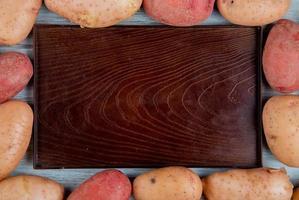 Draufsicht von rostroten und roten Kartoffeln, die in quadratischer Form um leeres Tablett auf hölzernem Hintergrund gesetzt werden