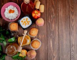 Draufsicht von Marmeladengläsern als Pfirsich und Pflaume mit Cupcakes Pfirsiche Hüttenkäse auf hölzernem Hintergrund verziert mit Blättern mit Kopienraum foto