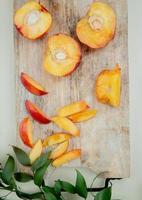Draufsicht von geschnittenen und geschnittenen Pfirsichen auf Schneidebrett auf weißem Hintergrund, verziert mit Blättern foto