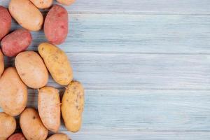 Draufsicht von rostroten weißen gelben und roten Kartoffeln auf der linken Seite und hölzernem Hintergrund mit Kopienraum
