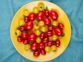 Draufsicht von Tomaten in Platte auf blauem Stoffhintergrund