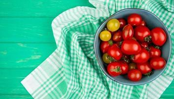 Draufsicht von Tomaten in der Schüssel auf Stoff auf der rechten Seite und grünem Hintergrund