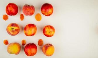 Draufsicht des Musters von geschnittenen und ganzen Pfirsichen auf der linken Seite und weißem Hintergrund mit Kopienraum foto