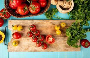 Draufsicht des Gemüses als Tomatenkoriander auf Schneidebrett mit schwarzem Pfeffer des Knoblauchbrechers auf blauem Hintergrund