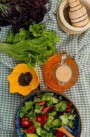 Draufsicht des Gemüsesalats mit geschmolzener Butter des Salatbasilikums-Knoblauchbrechers des schwarzen Pfeffers auf kariertem Stoffhintergrund