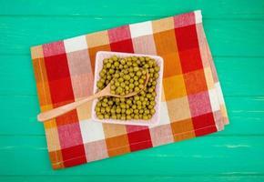 Draufsicht der Schüssel der grünen Erbse mit Holzlöffel auf Stoff und grünem Hintergrund