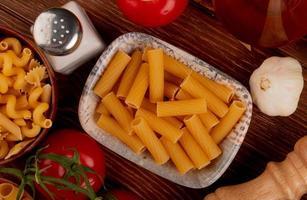 Draufsicht von Ziti-Nudeln mit verschiedenen Arten in Schüssel und Salz-Tomaten-Knoblauch auf hölzernem Hintergrund