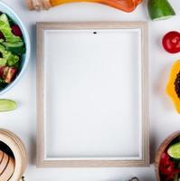 Draufsicht von Gemüsesalaten und Gemüse als Gurkentomate mit geschmolzener Butter des schwarzen Pfeffers und Rahmen auf weißem Hintergrund mit Kopienraum foto