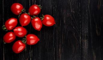 Draufsicht von Tomaten auf der linken Seite und hölzernem Hintergrund mit Kopienraum foto