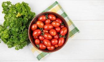 Draufsicht von Tomaten in der Schüssel mit chinesischem Koriander auf Stoff und hölzernem Hintergrund mit Kopienraum