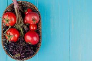 Draufsicht von Gemüse als Basilikum und Tomate im Korb auf der linken Seite und blauem Hintergrund mit Kopienraum foto