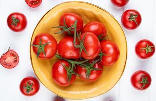 Draufsicht von Tomaten in der Schüssel mit geschnittenen und ganzen auf hölzernem Hintergrund foto