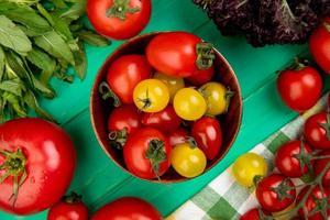 Draufsicht von Tomaten in der Schüssel mit grünen Minzblättern und Basilikum auf grünem Hintergrund