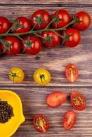 Draufsicht von Tomaten mit schwarzen Pfeffersamen auf hölzernem Hintergrund
