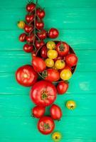 Draufsicht von Tomaten in der Schüssel mit anderen auf grünem Hintergrund