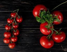 Draufsicht von Tomaten mit Koriander auf hölzernem Hintergrund