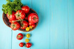 Draufsicht auf Gemüse als Koriander und Tomate im Korb auf der linken Seite und blauem Hintergrund mit Kopienraum foto