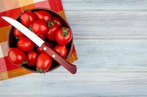 Draufsicht von Tomaten mit Messer in Schüssel auf Stoff und hölzernem Hintergrund mit Kopienraum foto