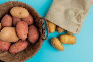 Draufsicht von Kartoffeln im Korb und von anderen, die aus Sack auf blauem Hintergrund verschüttet werden foto