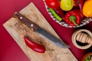 Draufsicht von Pfeffer und Messer auf Schneidebrett mit Gemüse im Korb und Knoblauchbrecher auf Bordo-Hintergrund foto