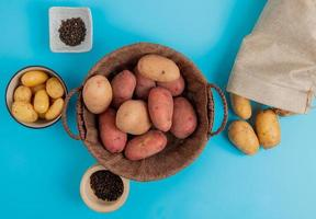 Draufsicht der Kartoffeln im Korb und in der Schüssel mit anderen, die aus Sack und schwarzen Pfeffersamen auf blauem Hintergrund verschüttet werden foto