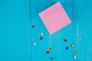Draufsicht der klebrigen Notiznotiz und der winzigen Stiftklammern auf blauem Hintergrund mit Kopienraum foto