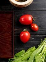 Draufsicht von Tomaten und grünen Minzblättern mit Tablett auf hölzernem Hintergrund