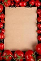 Draufsicht von Tomaten um Notizblock auf schwarzem Hintergrund mit Kopienraum foto