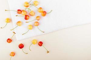 Draufsicht von Kirschen auf weißem Stoff und weißem Hintergrund mit Kopienraum foto