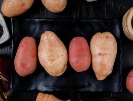 Draufsicht von Kartoffeln in Platte und auf hölzernem Hintergrund