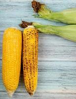 Draufsicht von Maiskolben auf hölzernem Hintergrund
