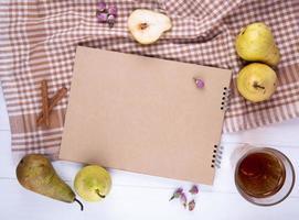 Draufsicht auf Skizzenbuch aus Bastelpapier mit frischen reifen Birnen und einem Glas Limonade auf karierter Tischdecke foto