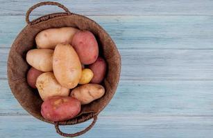 Draufsicht der Kartoffeln im Korb auf hölzernem Hintergrund mit Kopienraum foto
