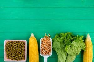 Draufsicht von Körnern und Maissamen mit grünem Erbsensalat auf grünem Hintergrund mit Kopienraum foto