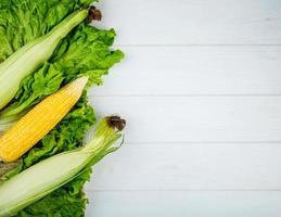 Draufsicht auf Hühneraugen mit Salat auf der linken Seite und weißem Hintergrund mit Kopienraum
