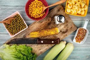 Draufsicht von Maiskolben und Messer auf Schneidebrett mit grünen Erbsen Maissamen Salatsalz auf hölzernem Hintergrund foto