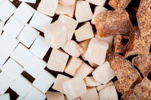 Draufsicht von weißen und braunen Zuckerwürfeln und Palmzuckerstücken verstreut auf dunklem hölzernem Hintergrund
