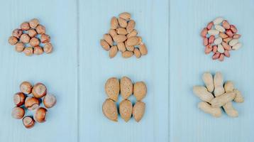 Draufsicht von gemischt von Nusshaufen isoliert auf blauem Hintergrund Mandeln Haselnüsse und Erdnüsse foto