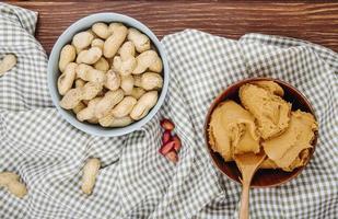 Draufsicht der Erdnussbutter in einer hölzernen Schüssel mit einer Schüssel, die mit Erdnüssen auf hölzernem Hintergrund gefüllt wird foto